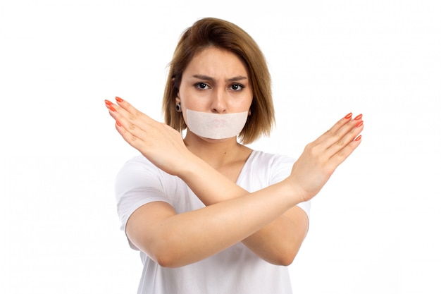 A front view young female in white t-shirt and black jeans wearing white bandage around her mouth showing ban sign on the white