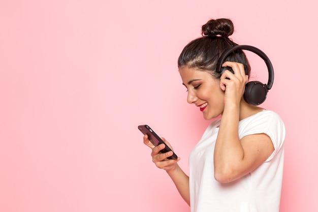 Una giovane femmina di vista frontale in maglietta e blue jeans bianche facendo uso di un telefono con il sorriso