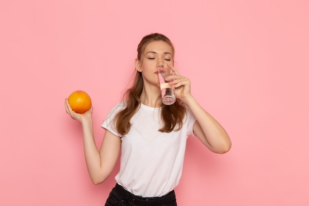 Front view of young female in white t-shirt holding fresh grapefruit and glass of water drinking on pink wall