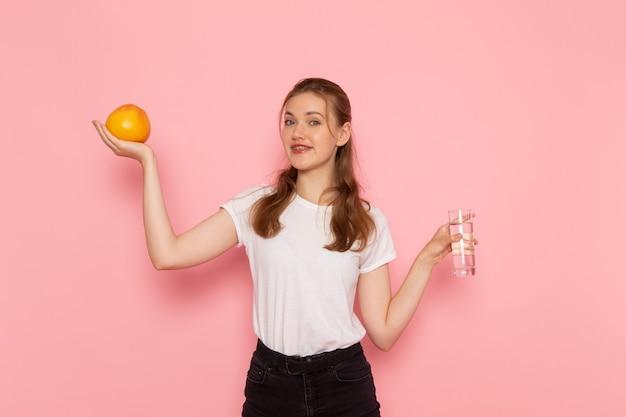 Vista frontale di giovane donna in maglietta bianca che tiene pompelmo fresco e bicchiere d'acqua sulla parete rosa