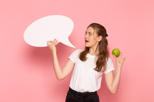 Vista frontale di giovane donna in maglietta bianca che tiene mela verde fresca e grande segno bianco sulla parete rosa chiaro
