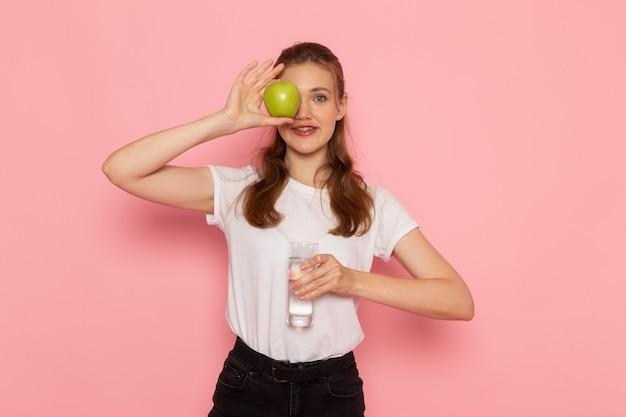 Vista frontale di giovane donna in maglietta bianca che tiene mela verde fresca e bicchiere d'acqua sulla parete rosa