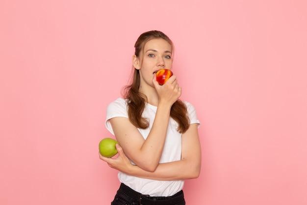 Vista frontale di giovane donna in maglietta bianca che tiene mela verde fresca con pesca che mangia sulla parete rosa chiaro