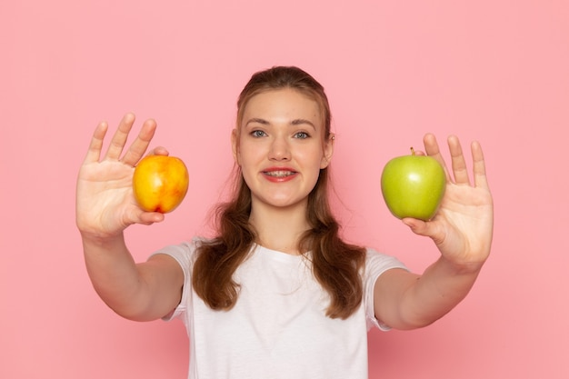 Front view of young female in white t-shirt holding fresh green apple with peach smiling on light-pink wall