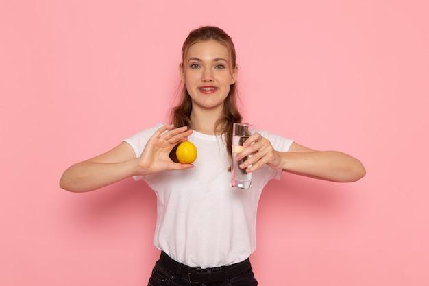 Vista frontale di giovane donna in maglietta bianca che tiene limone fresco e bicchiere d'acqua sulla parete rosa