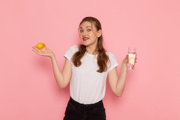 Vista frontale di giovane donna in maglietta bianca che tiene limone fresco e bicchiere d'acqua