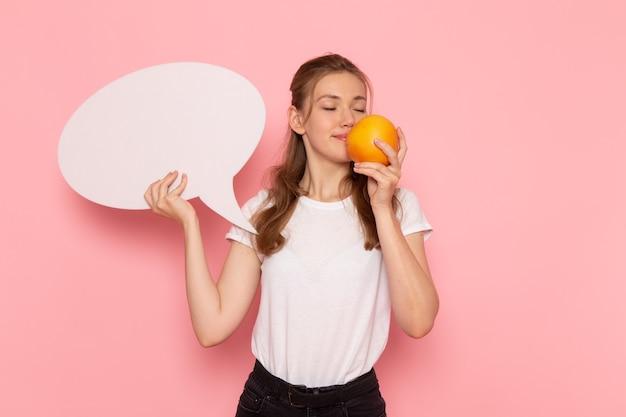 Vista frontale di giovane donna in maglietta bianca che tiene pompelmo e segno bianco sulla parete rosa chiaro