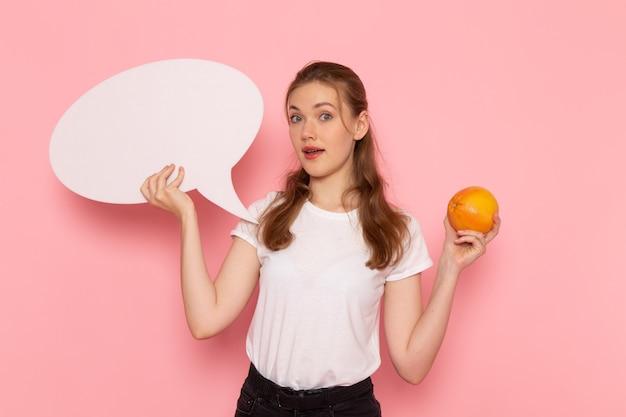 Vista frontale di giovane donna in maglietta bianca che tiene pompelmo e segno bianco sulla parete rosa