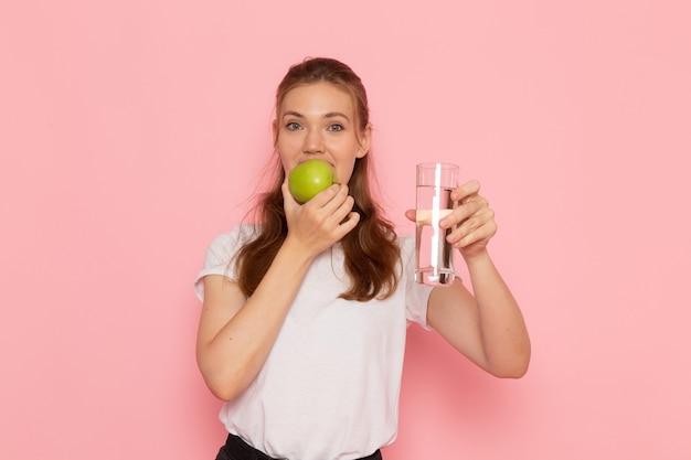 Vista frontale di giovane donna in maglietta bianca che tiene mela verde e bicchiere d'acqua sulla parete rosa