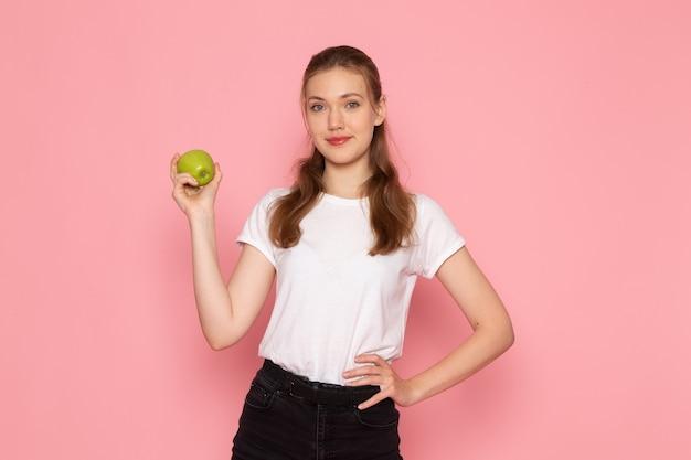 Vista frontale di giovane donna in maglietta bianca che tiene mela verde sulla parete rosa