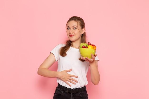 Vista frontale della giovane donna in t-shirt bianca tenendo il piatto con frutta fresca sorridente sulla parete rosa chiaro