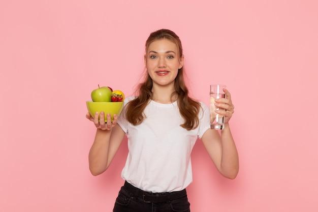 Vista frontale della giovane donna in t-shirt bianca tenendo il piatto con frutta e bicchiere d'acqua sulla parete rosa
