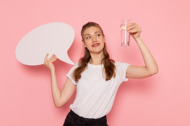 Vista frontale della giovane donna in maglietta bianca con cartello bianco e bicchiere d'acqua sorridente sulla parete rosa