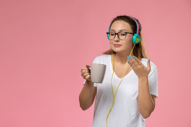 Front view young female in white t-shirt just listening to music via earphones and holding cup with tea on pink background
