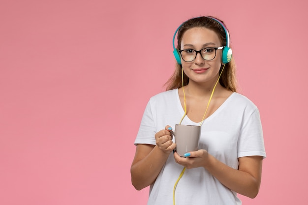 Front view young female in white t-shirt just listening to music via earphones and holding cup with tea on the pink background