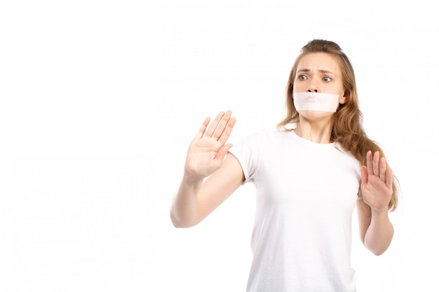 A front view young female in white t-shirt with white bandage around her mouth afraid careful on the white