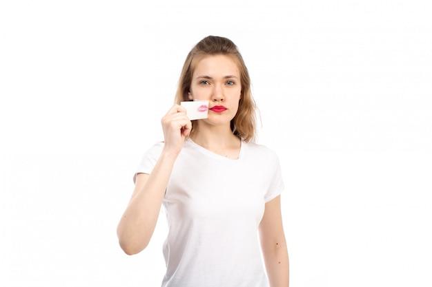 Una giovane femmina di vista frontale in maglietta bianca con la fasciatura bianca intorno alla sua bocca che la toglie sul bianco