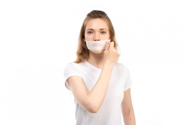 A front view young female in white t-shirt with white bandage around her mouth taking it off on the white