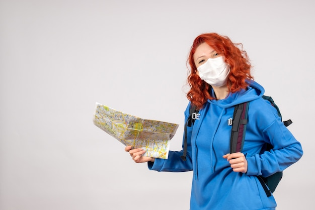 Front view of young female with backpack and map in mask on the white wall