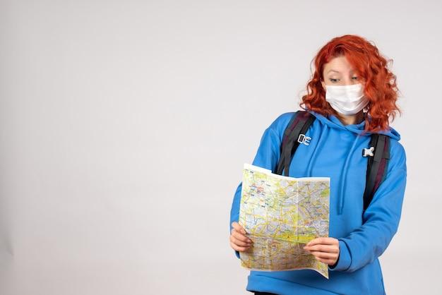Vista frontale della giovane donna con zaino e mappa in maschera sul muro bianco
