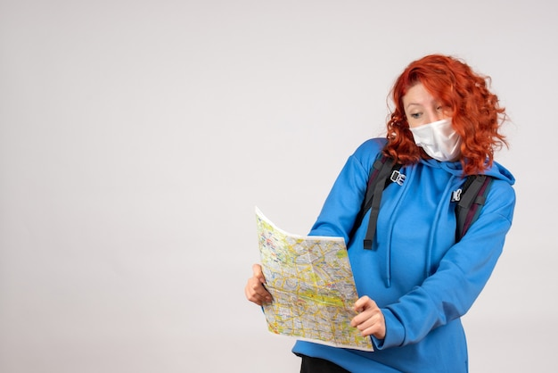 Front view of young female with backpack and map in mask on white wall