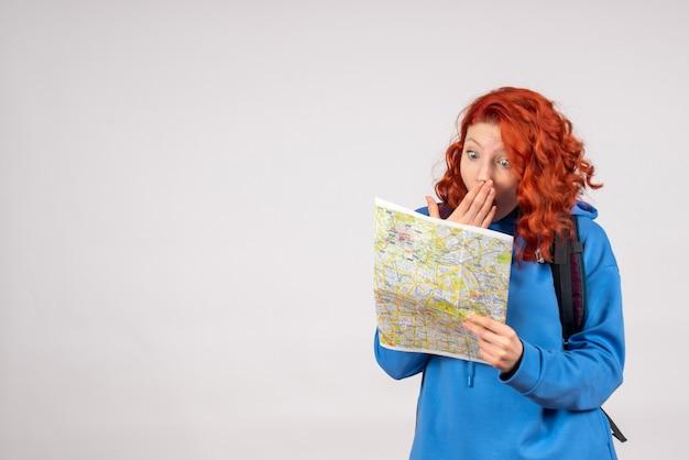Vista frontale della giovane donna con zaino e mappa sul muro bianco
