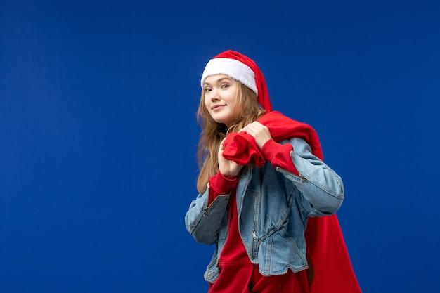 Вид спереди молодая женщина с сумкой, полной подарков на синем фоне, эмоции, праздник, рождество