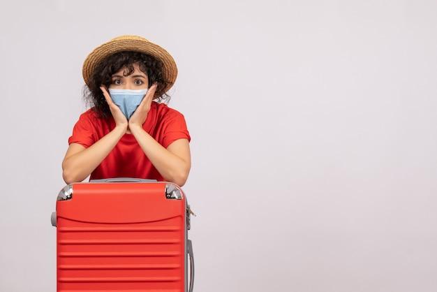 Вид спереди молодая женщина с сумкой в маске на белом фоне, цвет covid- пандемический вирус солнца, поездка, туристические каникулы