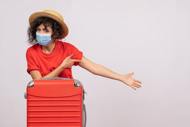 Вид спереди молодая женщина с сумкой в маске на белом фоне, цвет covid- путешествие, отпуск, пандемия, вирус солнца, поездка, турист