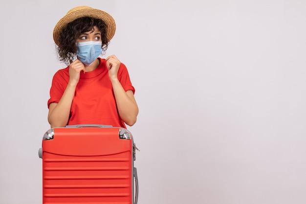 Вид спереди молодая женщина с сумкой в маске на белом фоне, вирус covid- туристическое солнце, пандемия, отпуск, цветная поездка