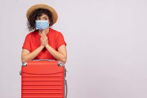 白い背景色のcovid-パンデミック太陽ウイルス旅行観光休暇にマスクにバッグを持つ正面の若い女性