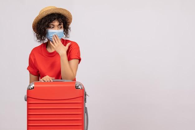 Вид спереди молодая женщина с сумкой в маске на белом фоне, цвет covid- отпуск, пандемия солнечного вируса, туристическая поездка