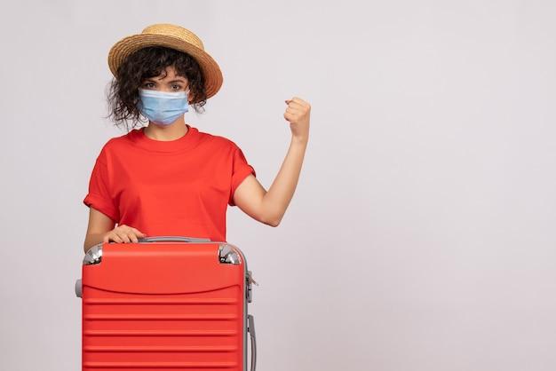 Вид спереди молодая женщина с сумкой в маске на белом фоне, вирус covid- туристическая пандемия, отпуск, цветная поездка, солнце