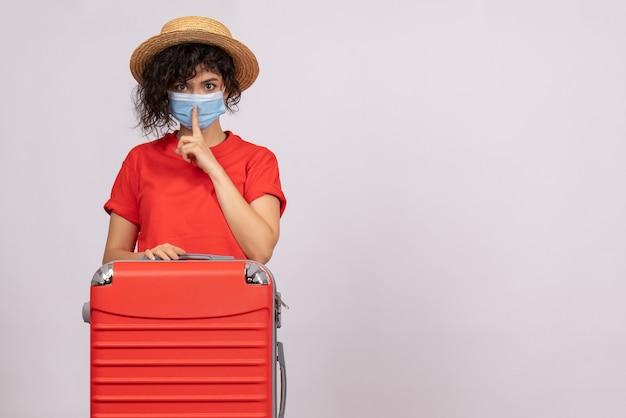 白い背景色のcovid-パンデミック太陽ウイルス観光休暇にマスクにバッグを持つ正面の若い女性