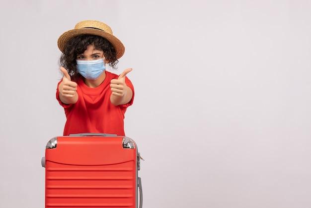 Вид спереди молодая женщина с сумкой в маске на белом фоне, цвет covid- отпуск поездки солнечный туристический вирус