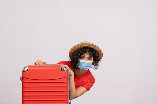 Молодая женщина с сумкой в маске на белом фоне, вид спереди, туристический отдых, поездка по пандемическому вирусу