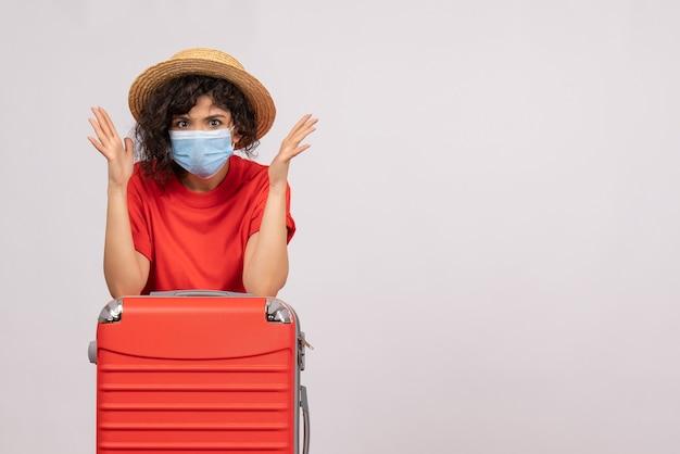 Вид спереди молодая женщина с сумкой в маске на белом фоне цвета covid- пандемический отпуск поездка солнечный туристический вирус