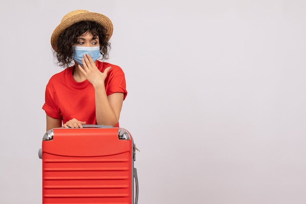 Front view young female with bag in mask on the white background color covid- vacation pandemic sun virus trip tourist