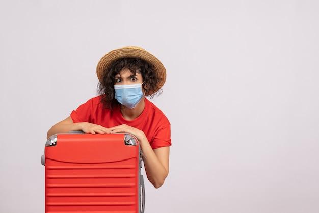 Vista frontale giovane donna con borsa in maschera su sfondo bianco colore covid- viaggio turistico vacanza pandemia sole viaggio