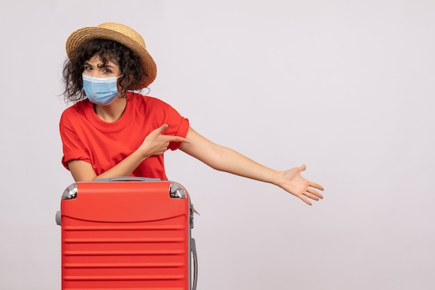 Front view young female with bag in mask on a white background color covid- voyage vacation pandemic sun virus trip tourist