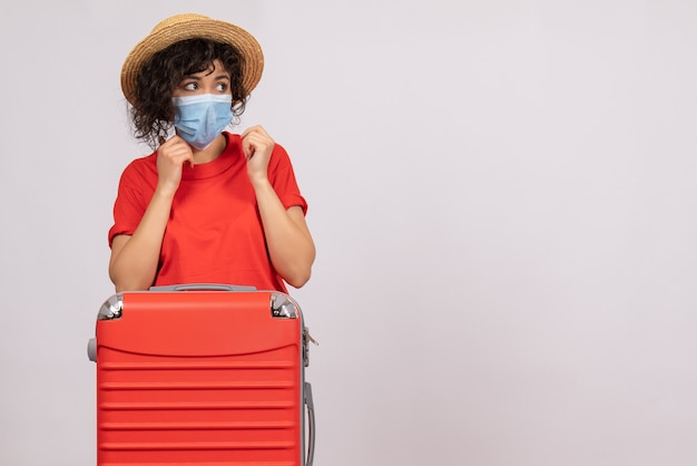 Front view young female with bag in mask on a white background virus covid- tourist sun pandemic vacation color trip