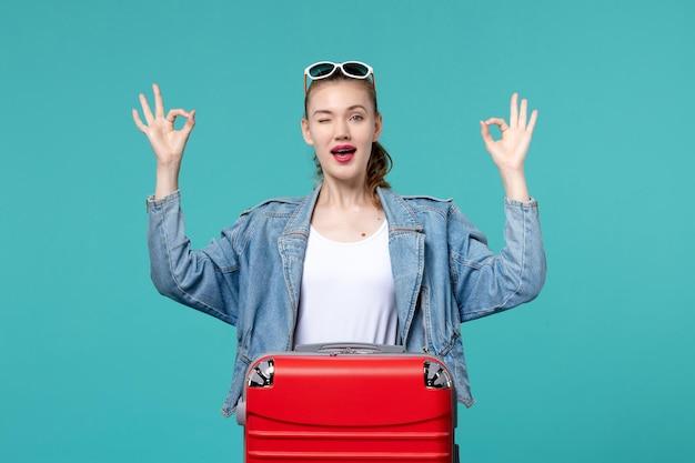 青いスペースで休暇の準備をしているバッグを持つ若い女性の正面図