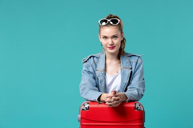 가방이 푸른 공간에서 휴가를 준비하는 전면보기 젊은 여성
