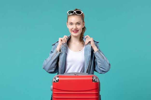 Вид спереди молодая женщина с сумкой, готовящаяся к отпуску на синем столе