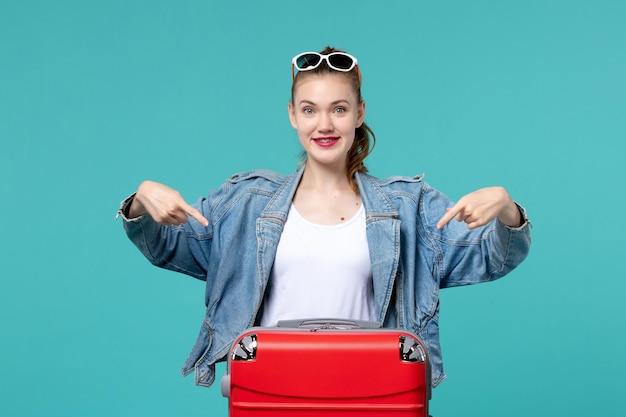 Giovane femmina di vista frontale con la borsa che prepara per la vacanza sullo spazio blu