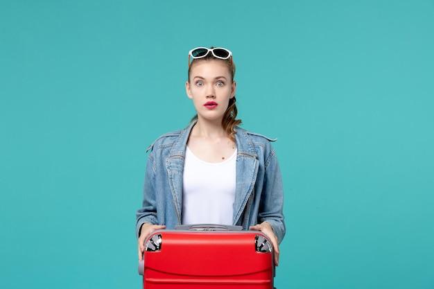 Giovane femmina di vista frontale con la borsa che prepara per la vacanza sullo spazio blu-chiaro