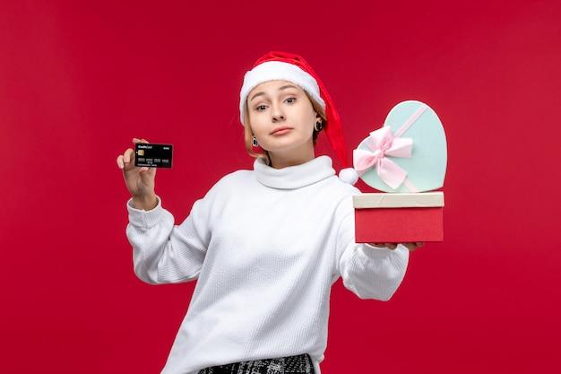 Вид спереди молодая женщина с банковской картой и подарками на красном фоне