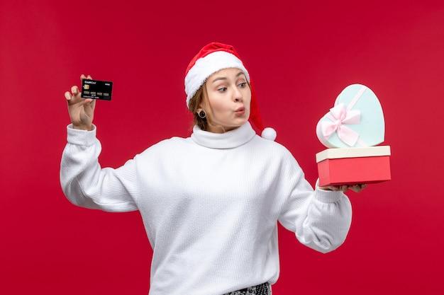 Вид спереди молодая женщина с банковской картой и подарками на красном столе