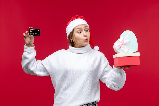 Front view young female with bank card and gifts on red desk