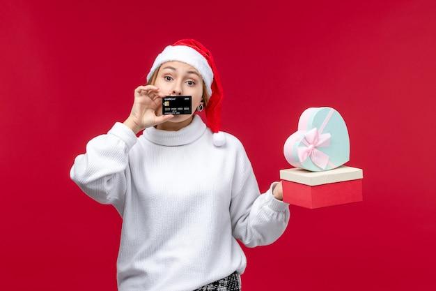 Giovane femmina di vista frontale con carta di credito e regali sullo scrittorio rosso